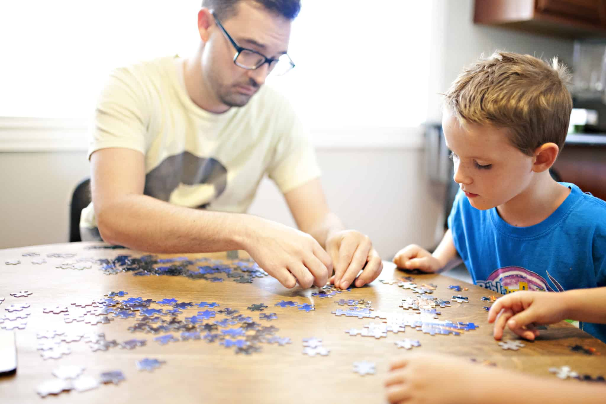 pai a fazer um puzzle em cima da mesa com o filho ao lado