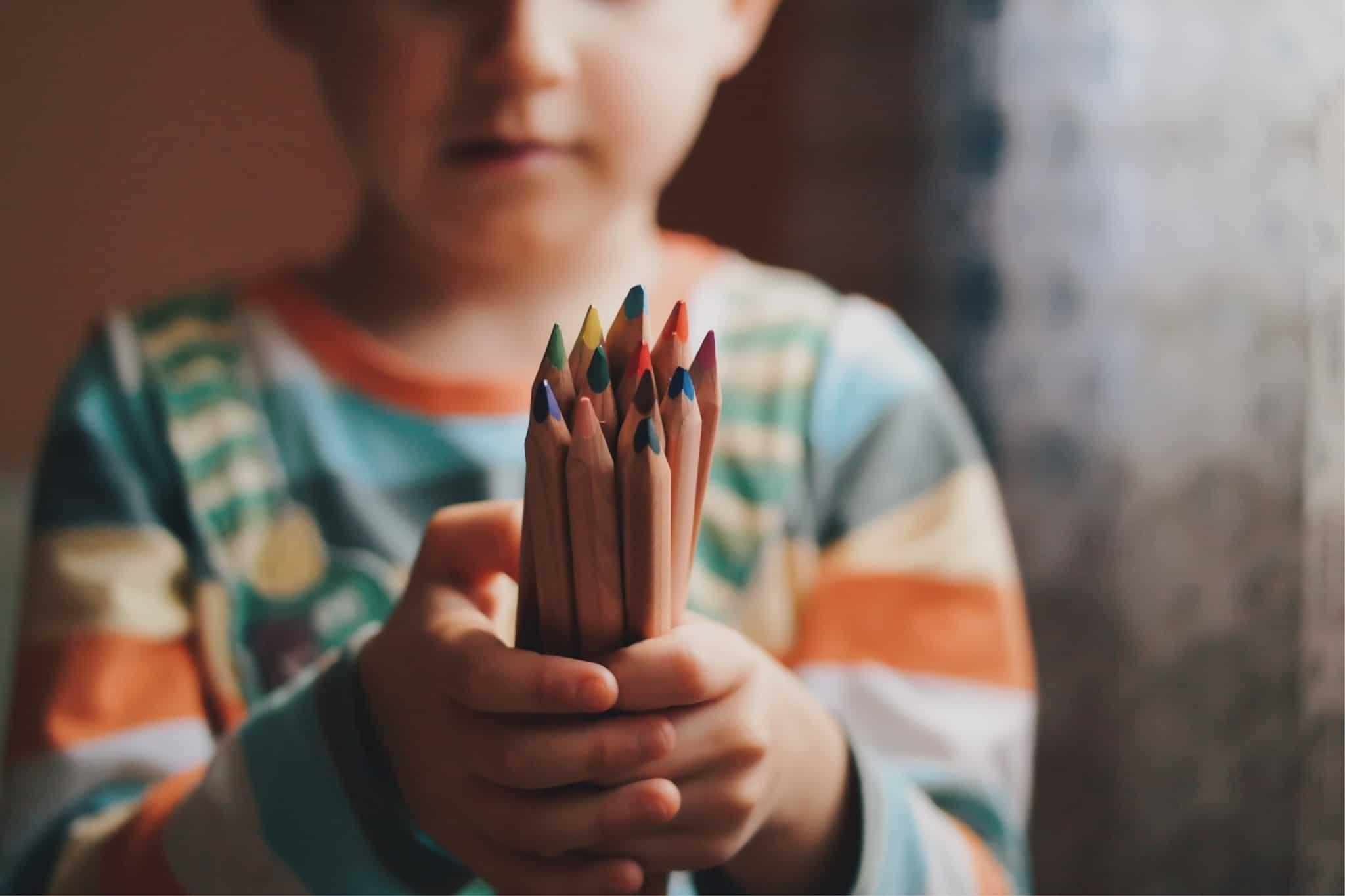 criança a segurar lápis de cor