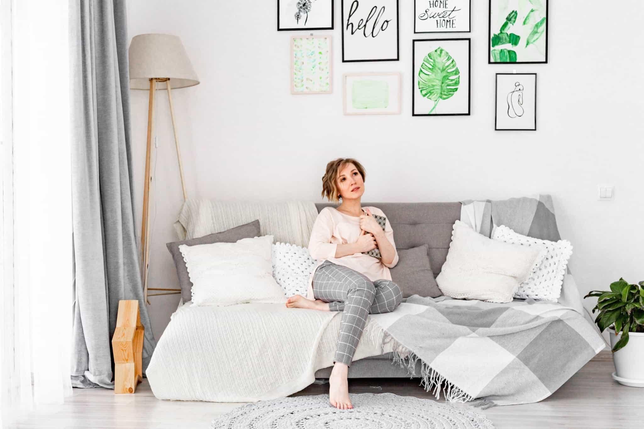 mulher pensativa sentada no sofá a agarrar um caderno