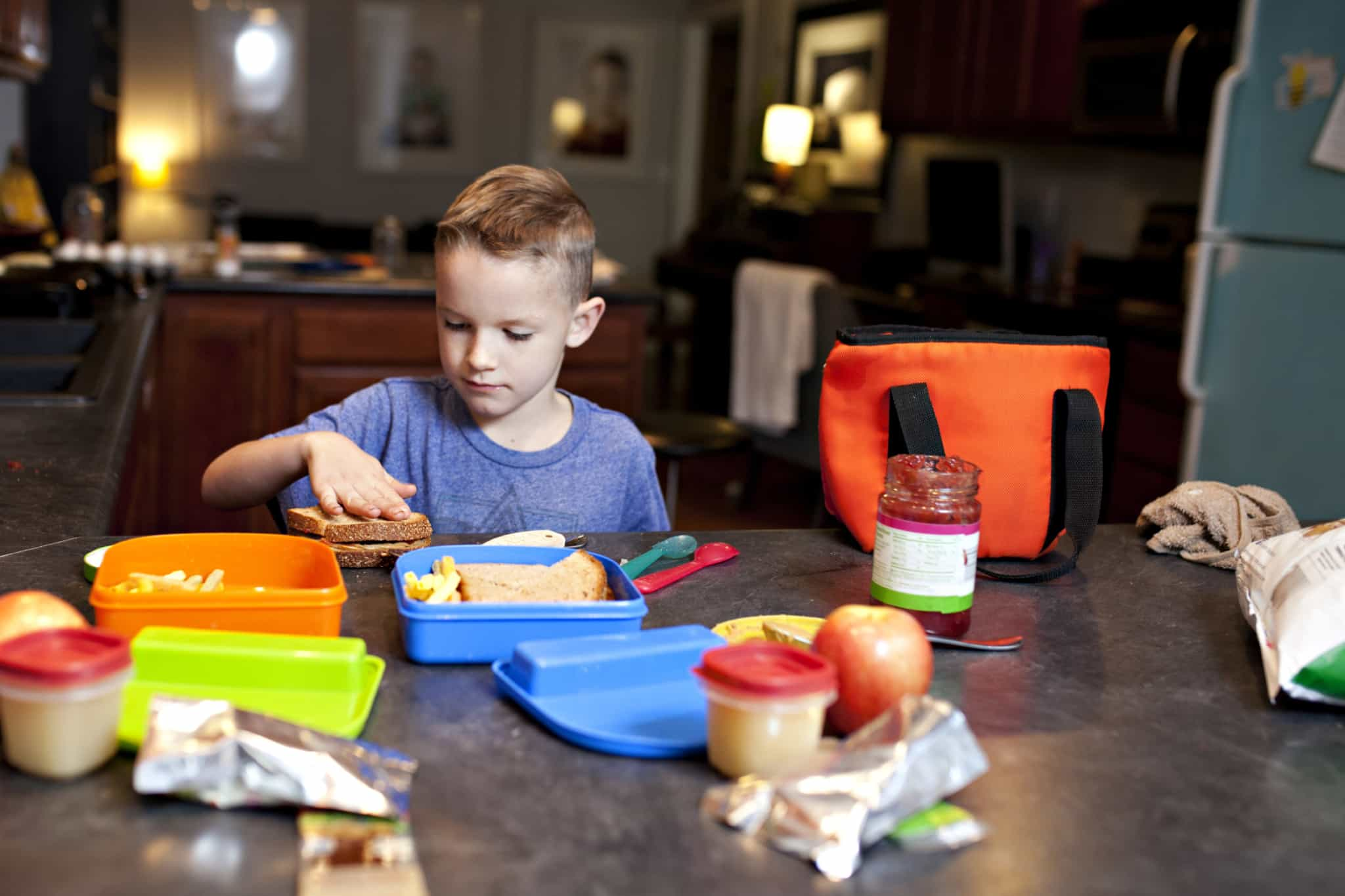 rapaz loiro na cozinha a preparar o seu almoço para a escola