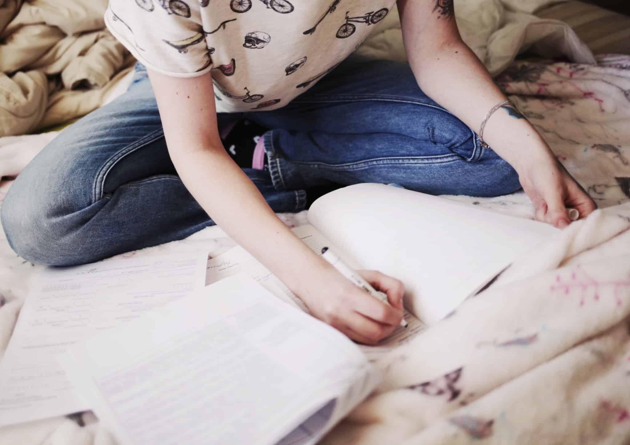 rapariga sentada em cima da cama a escrever em papel