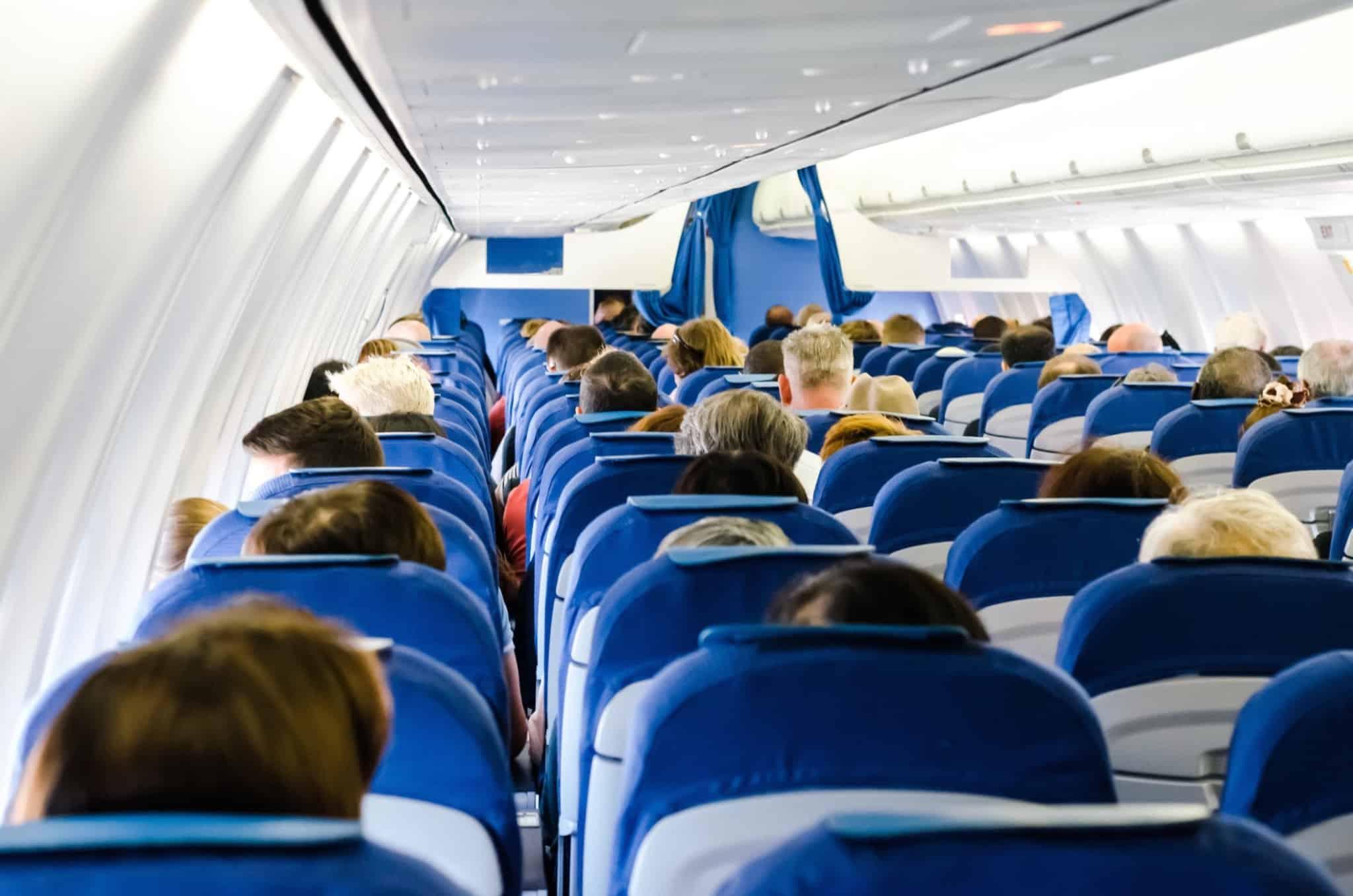 pessoas sentadas num avião com assentos azuis