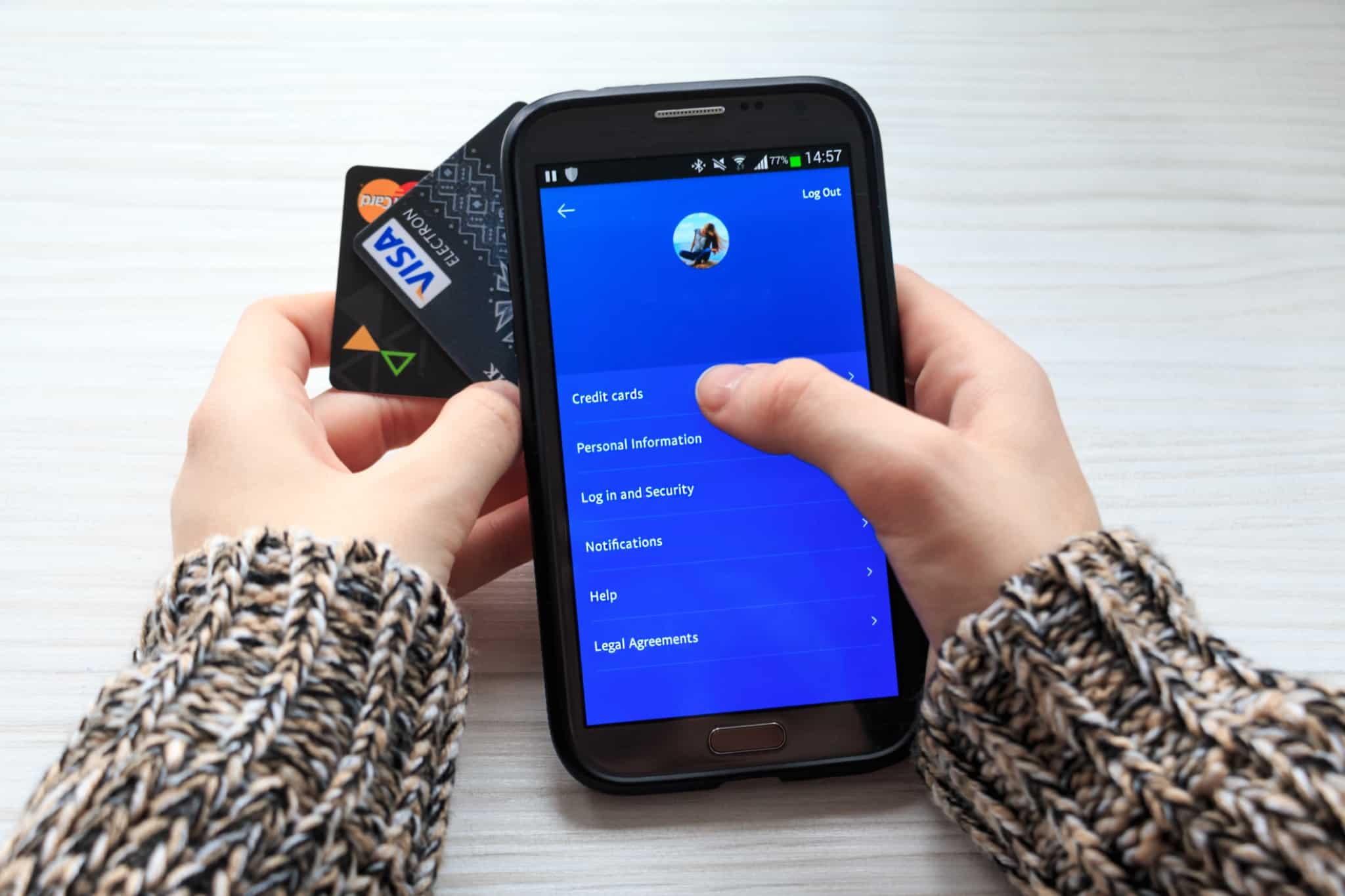 pessoa com cartões de crédito a mexer numa app de fundo azul