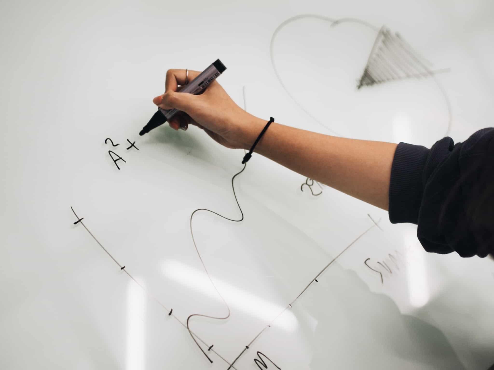 pessoa com caneta de feltro a escrever fórmulas