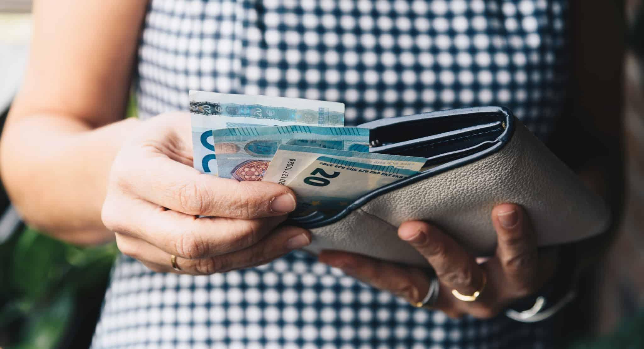 mulher com carteira aberta e notas de vinte euros