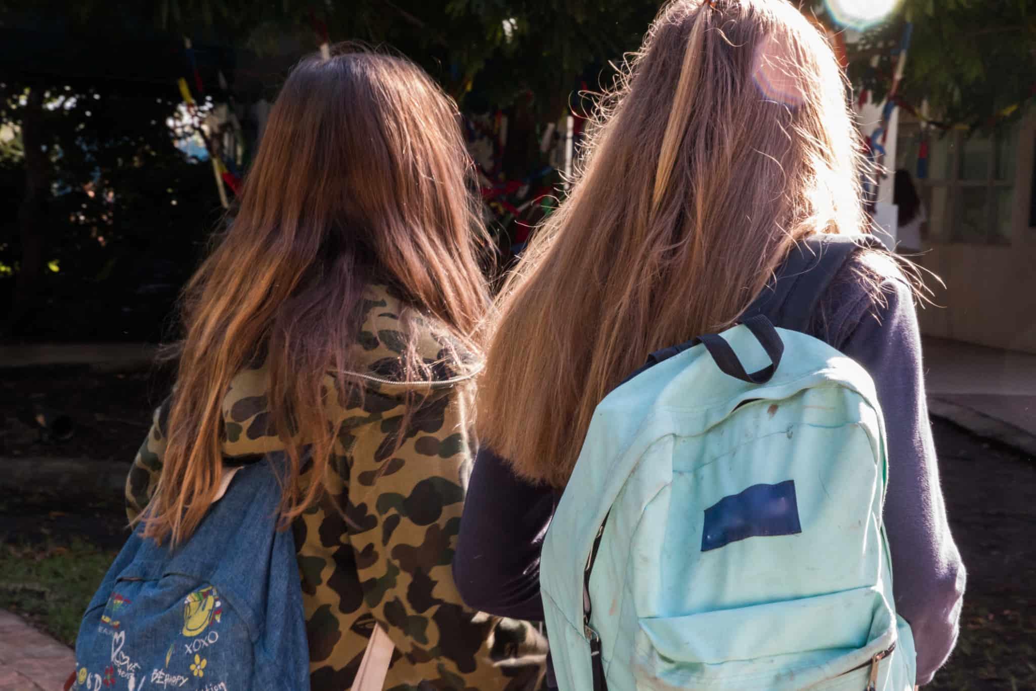 raparigas de malas às costas a ir para a escola