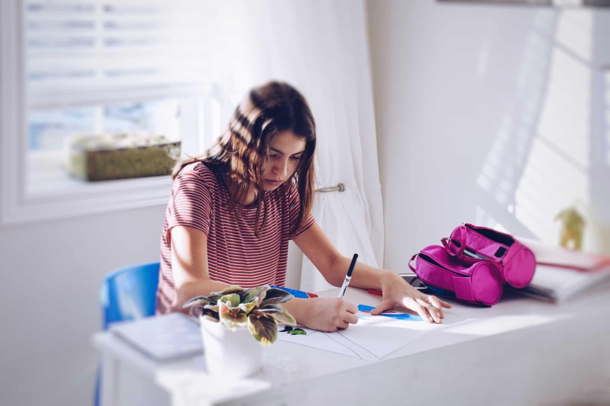 rapariga a estudar numa secretária em casa