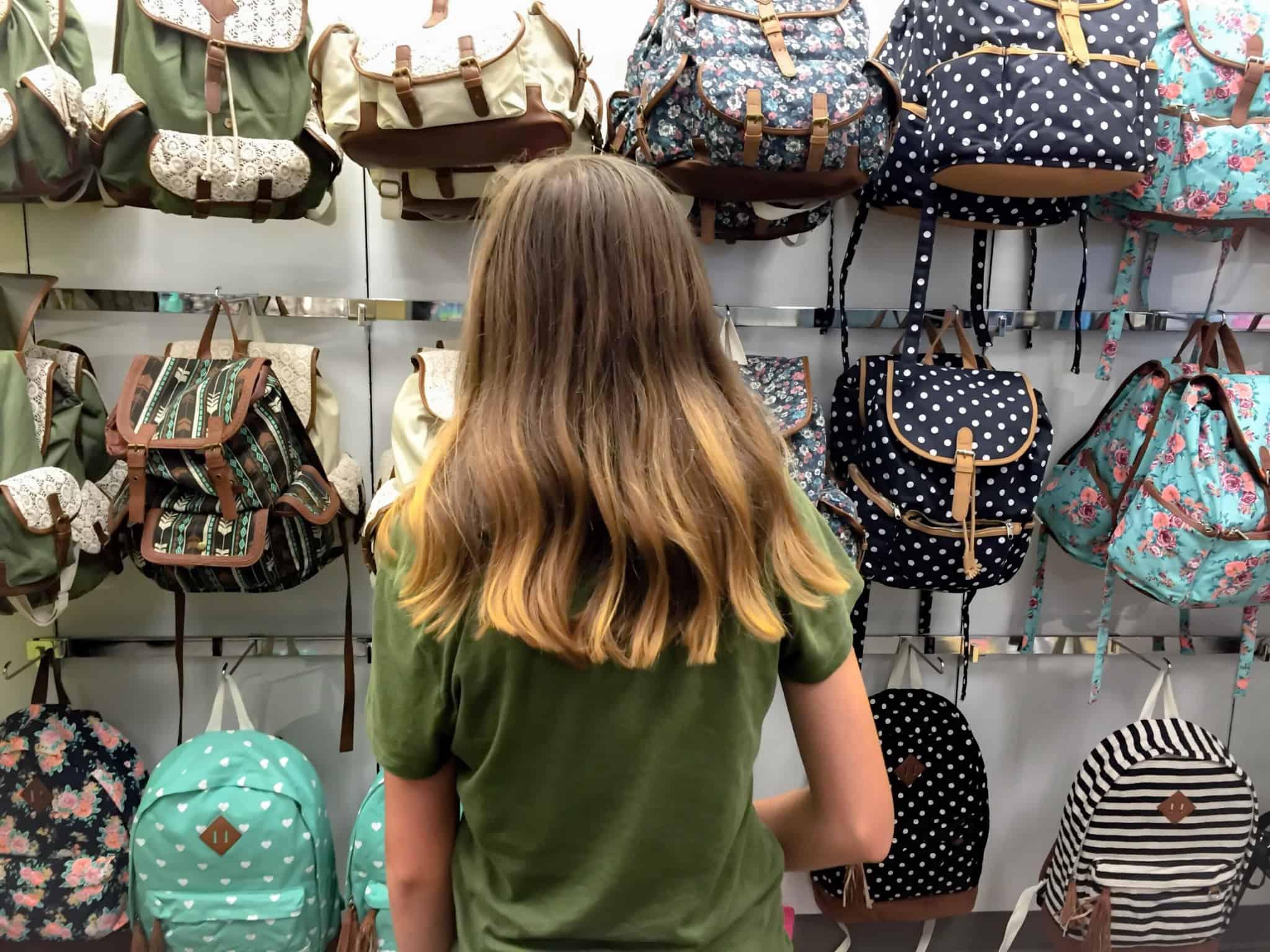 rapariga adolescente a ver malas numa loja