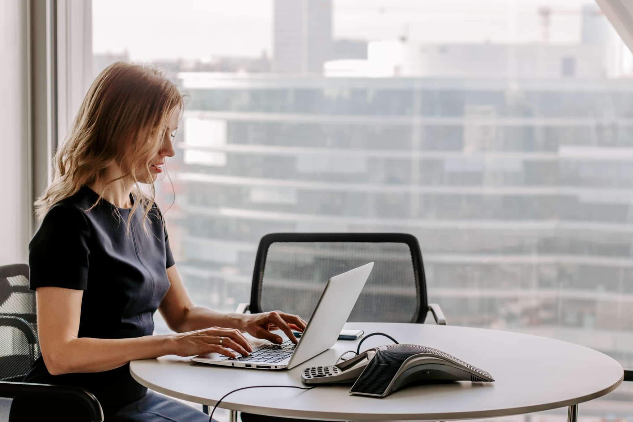 mulher a trabalhar com o portátil em cima de uma mesa