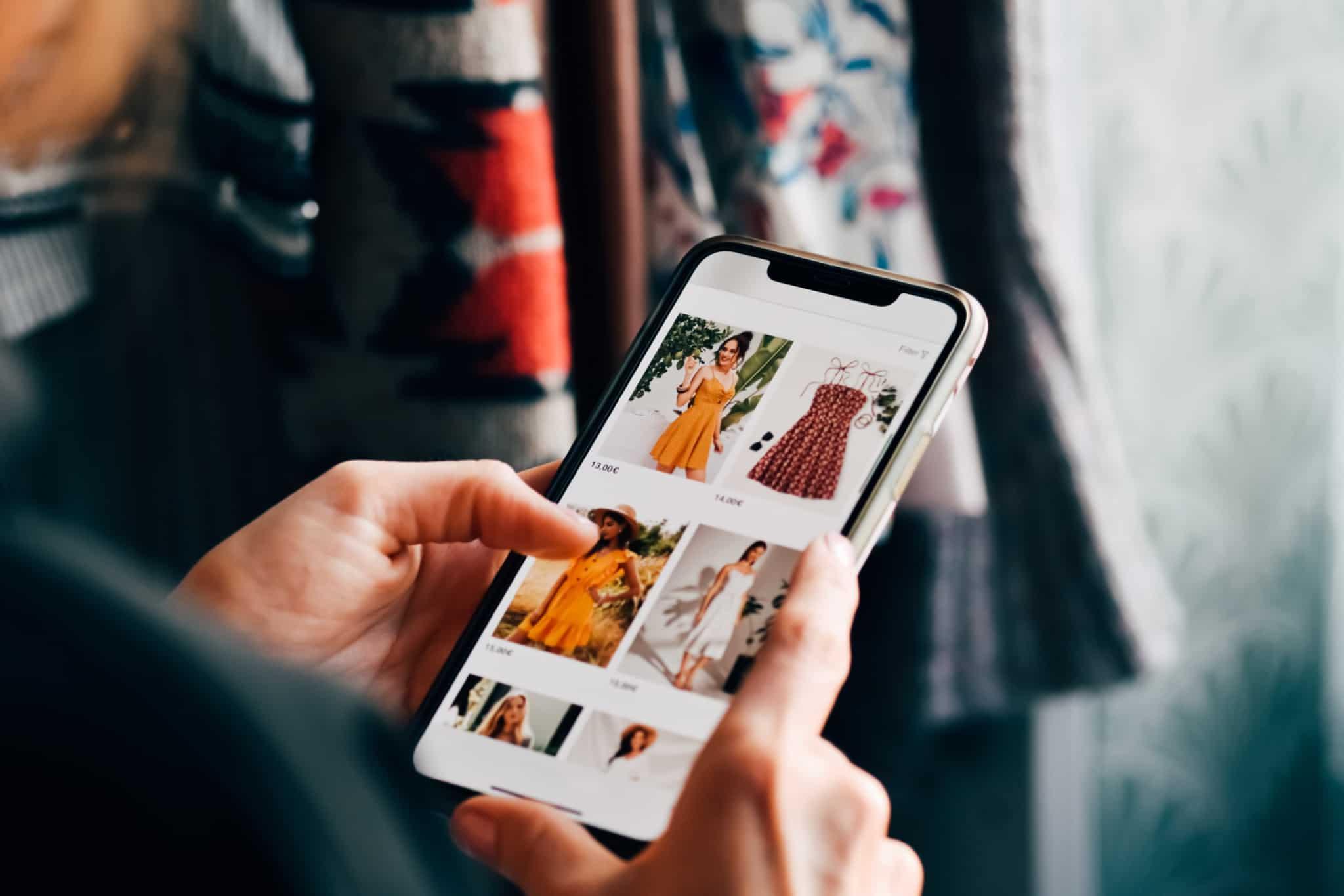 pessoa a mexer no telemóvel a ver vestidos online