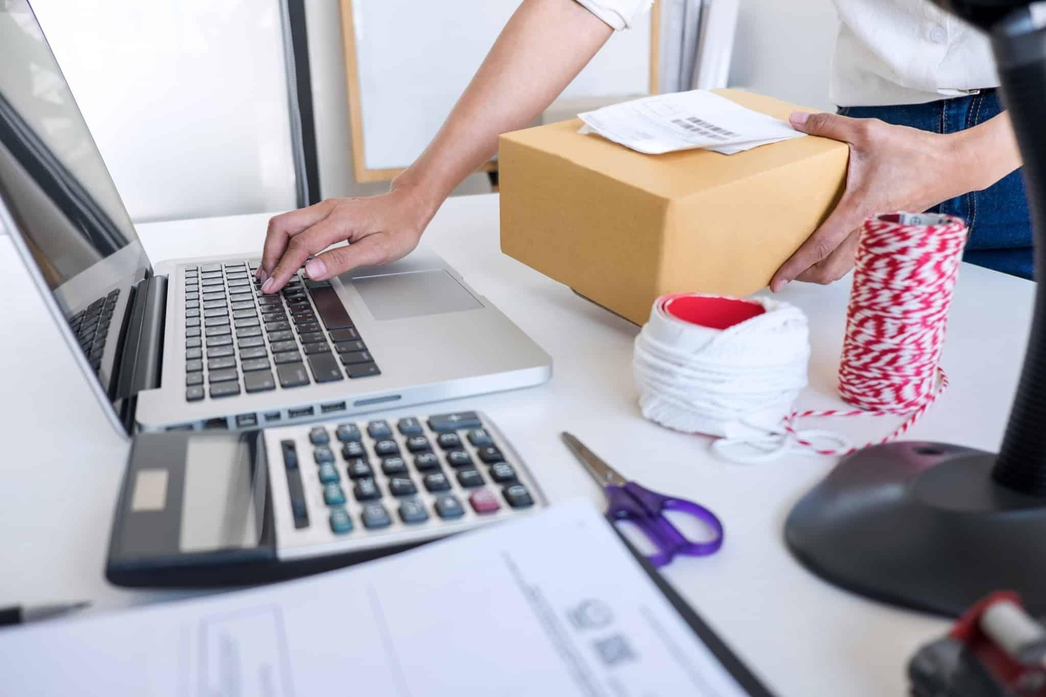 mulher a mexer no computador e a tratar de encomendas da sua loja online