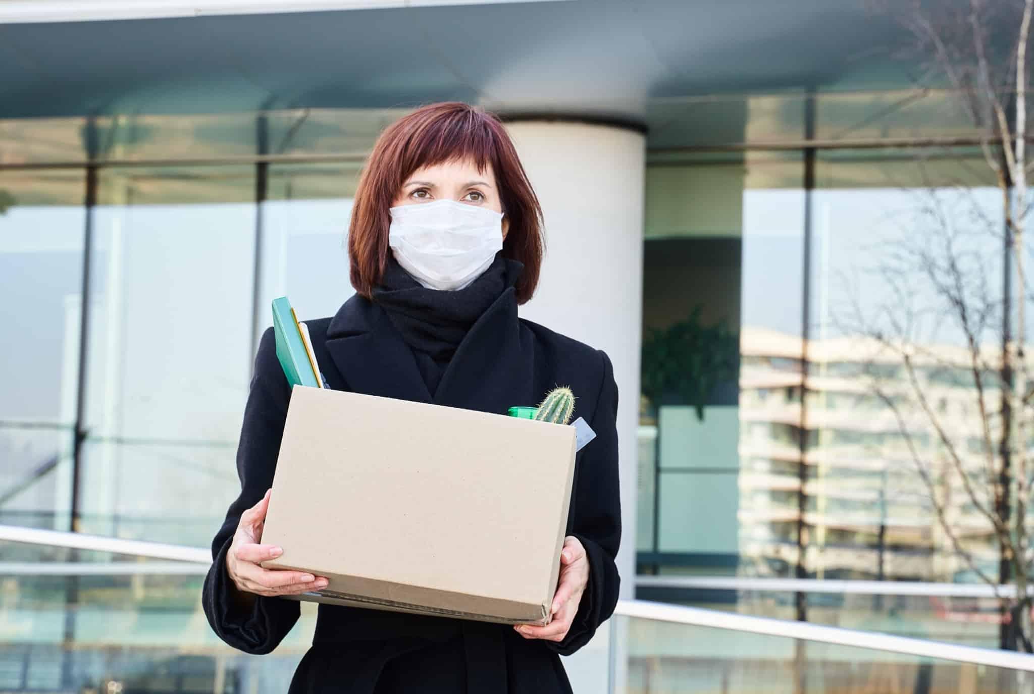 Mulher com máscara e caixa com os pertences do escritório