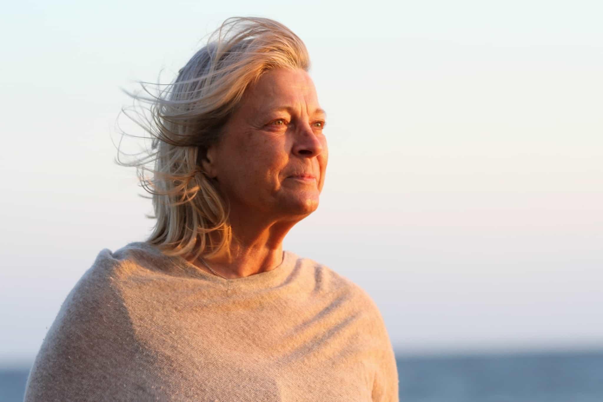 senhora com cabelo branco a olhar para o por do sol
