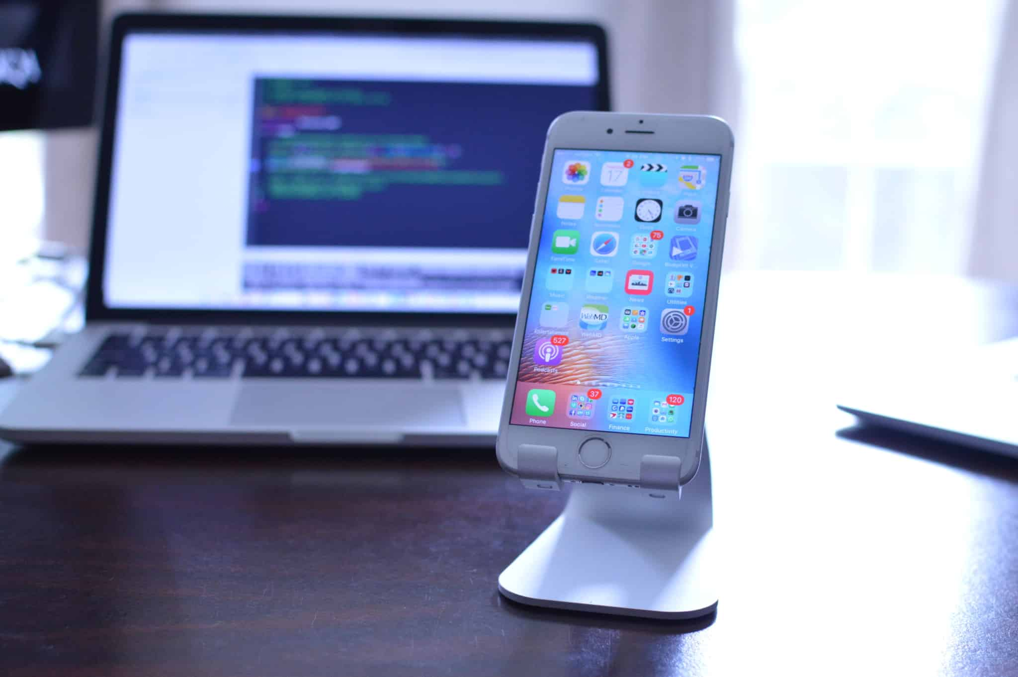 smartphone num tripé com um computador com código no ecrã