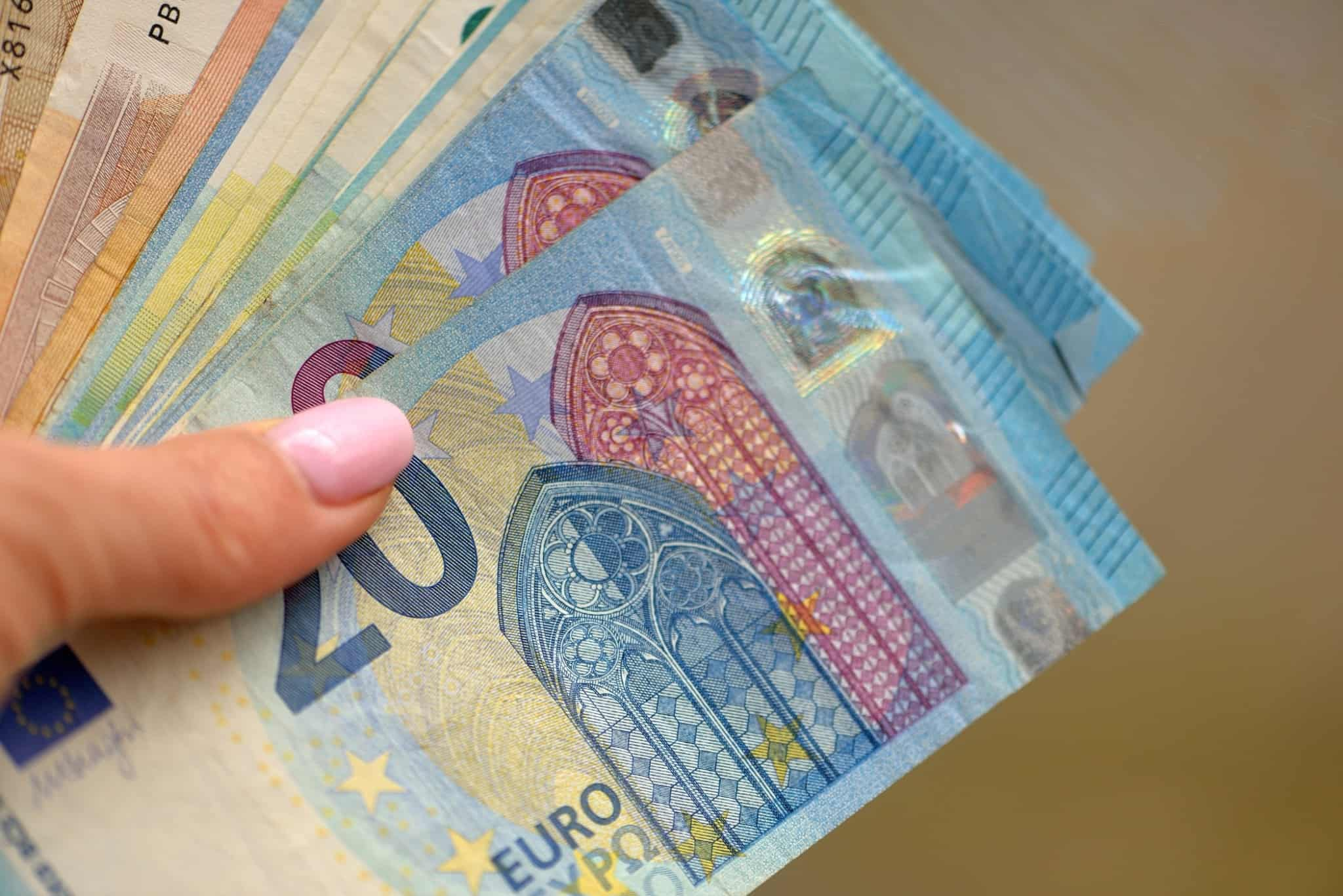 mulher de unha cor de rosa a segurar notas de vinte e dez euros