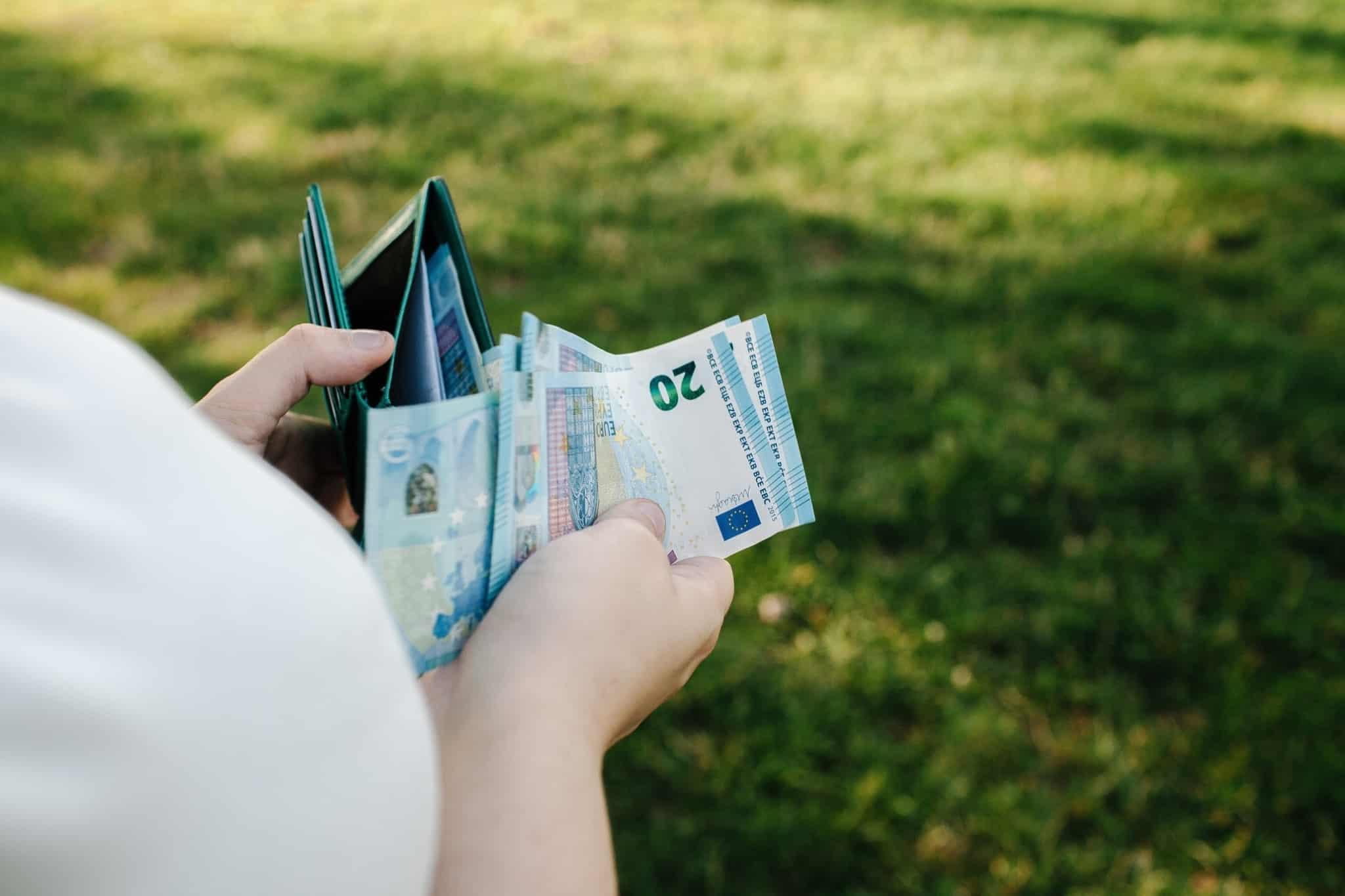 pessoa a tirar notas de vinte euros da carteira