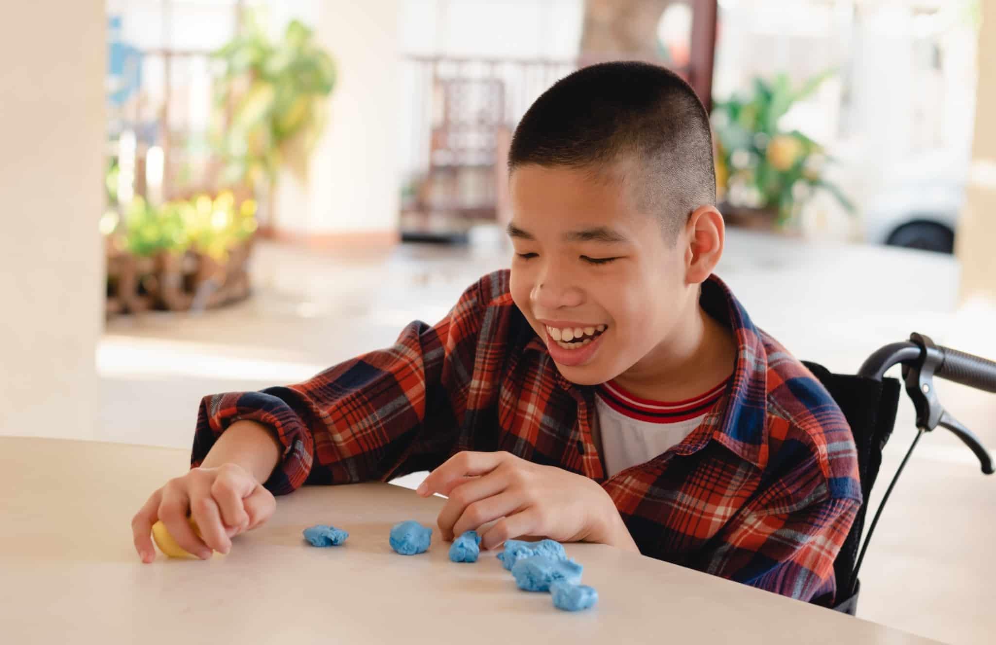 criança de cadeiras de rodas a brincar em cima da mesa