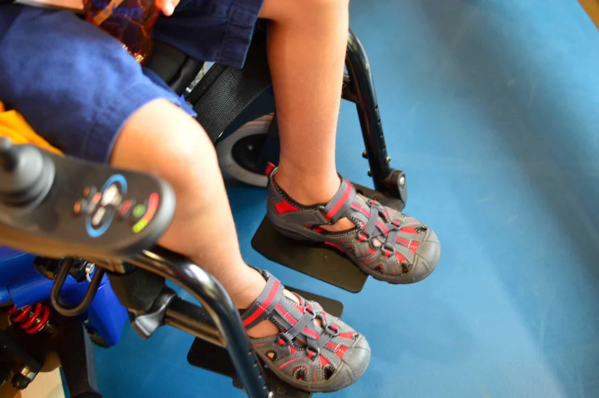 criança com sandálias vermelhas sentada em cadeira de rodas