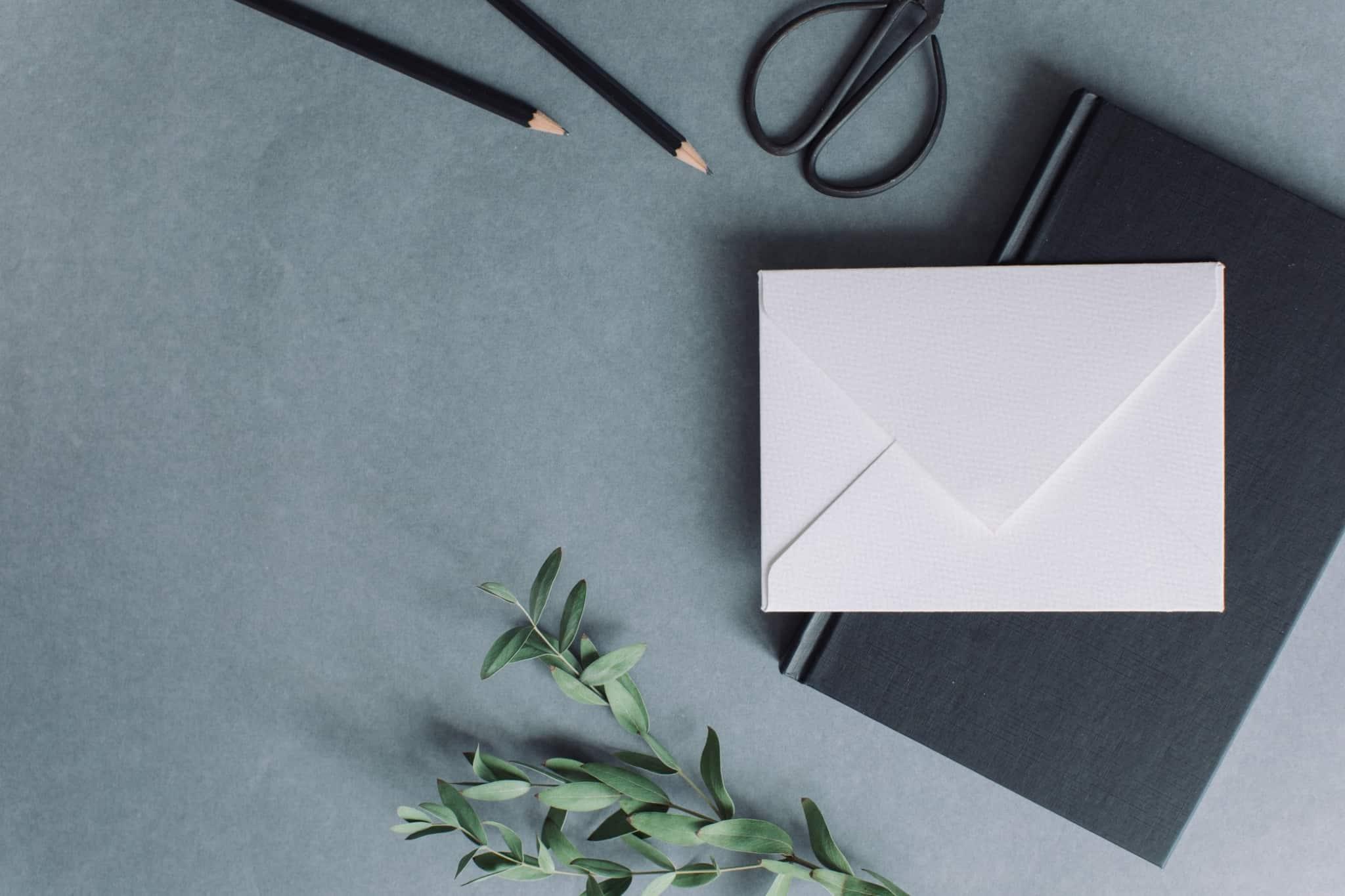 envelope branco em cima de um caderno preto