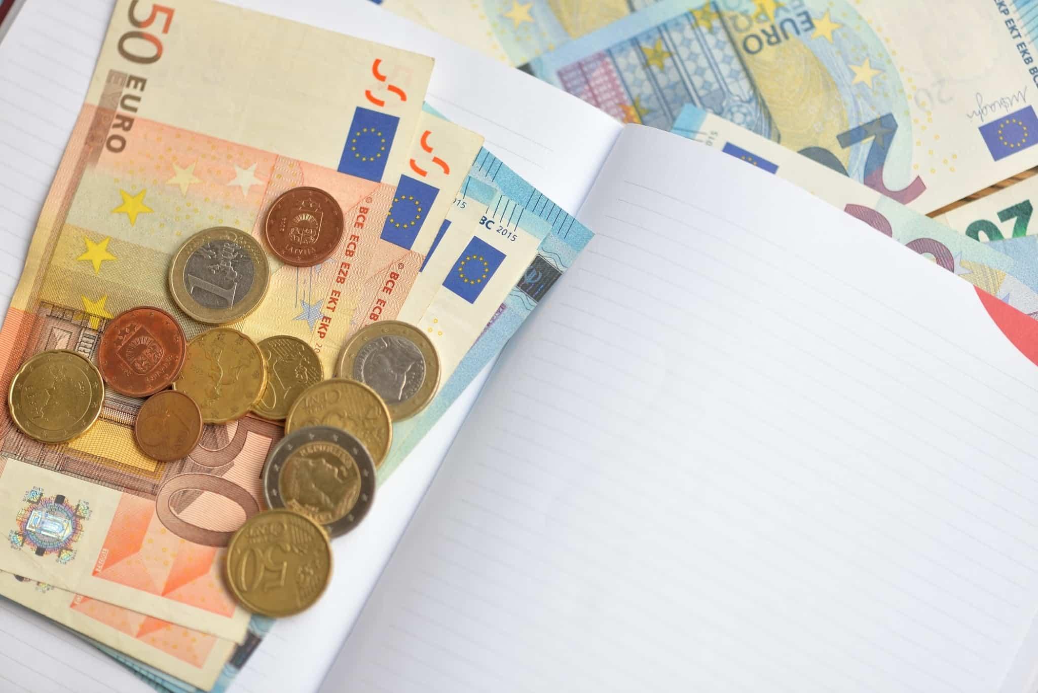 notas e moedas de euros dentro de um bloco de notas