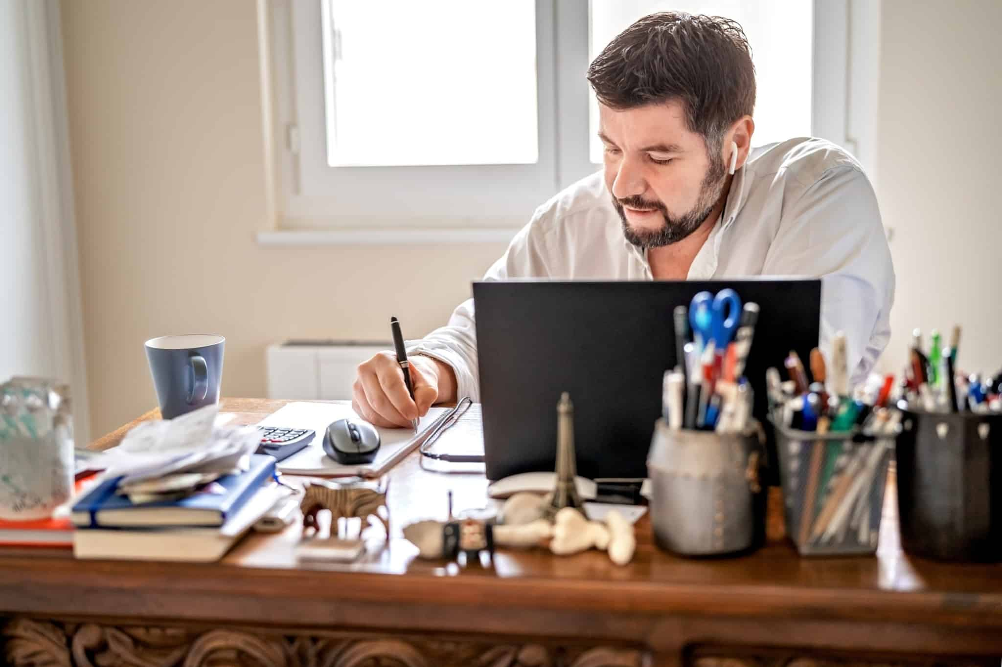 homem a trabalhar na secretária de casa