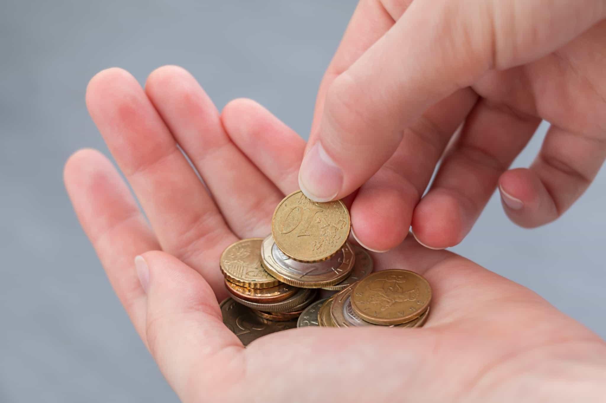 pessoa com moedas de euro na mão
