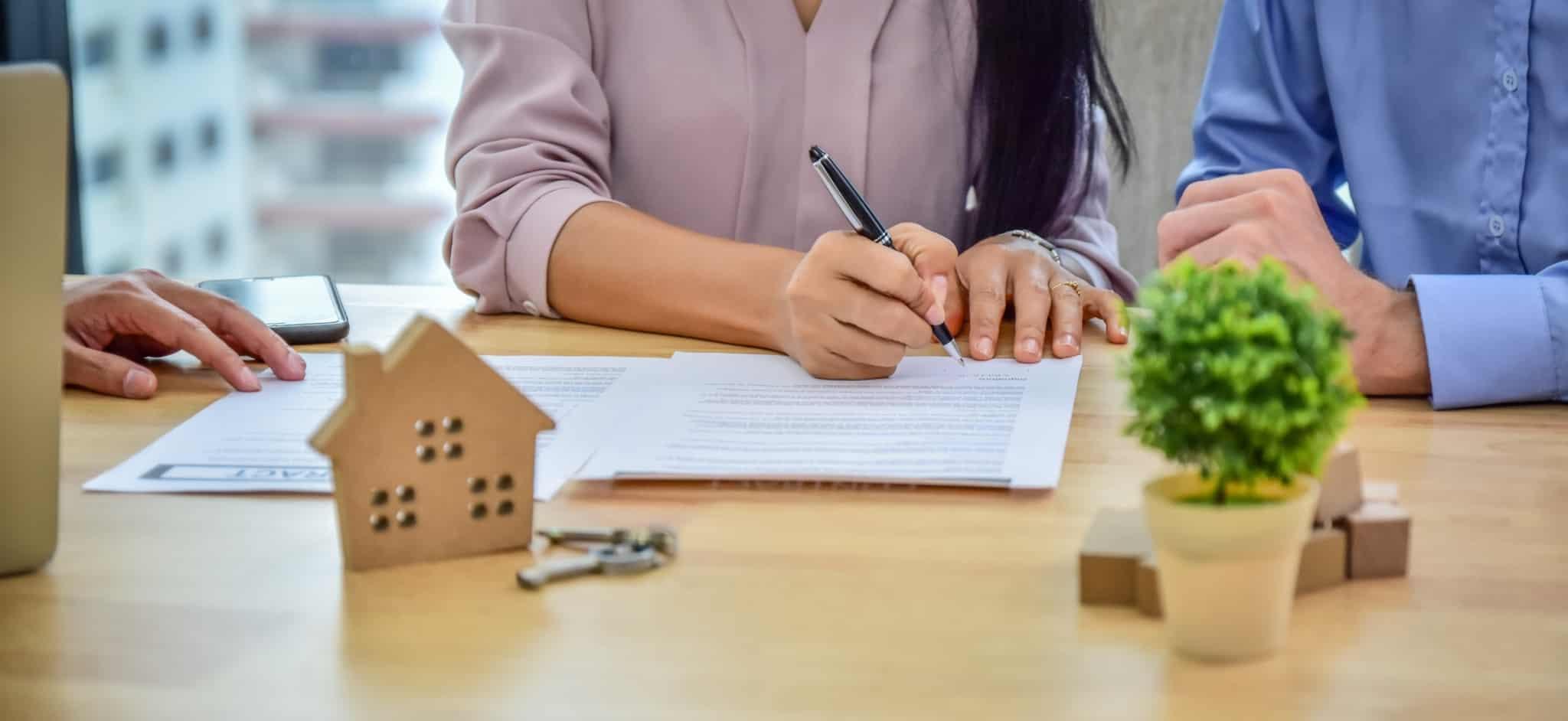 casal a assinar uns documentos com uma casa de madeira