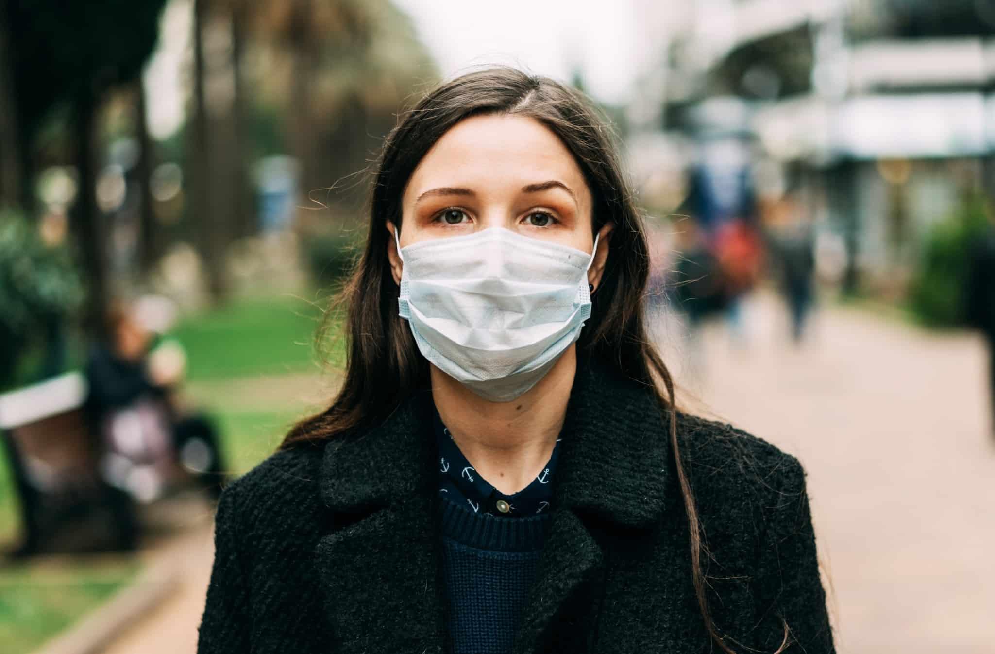 mulher na rua com máscara facial