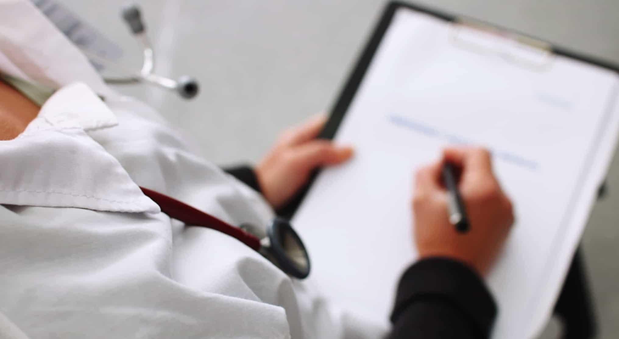Médica a assinar papéis