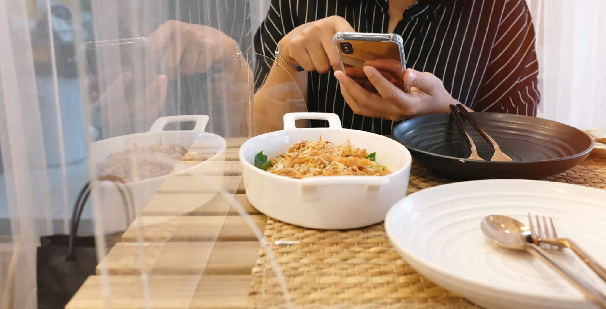 Mulher a comer num restaurante com um acrílico de proteção