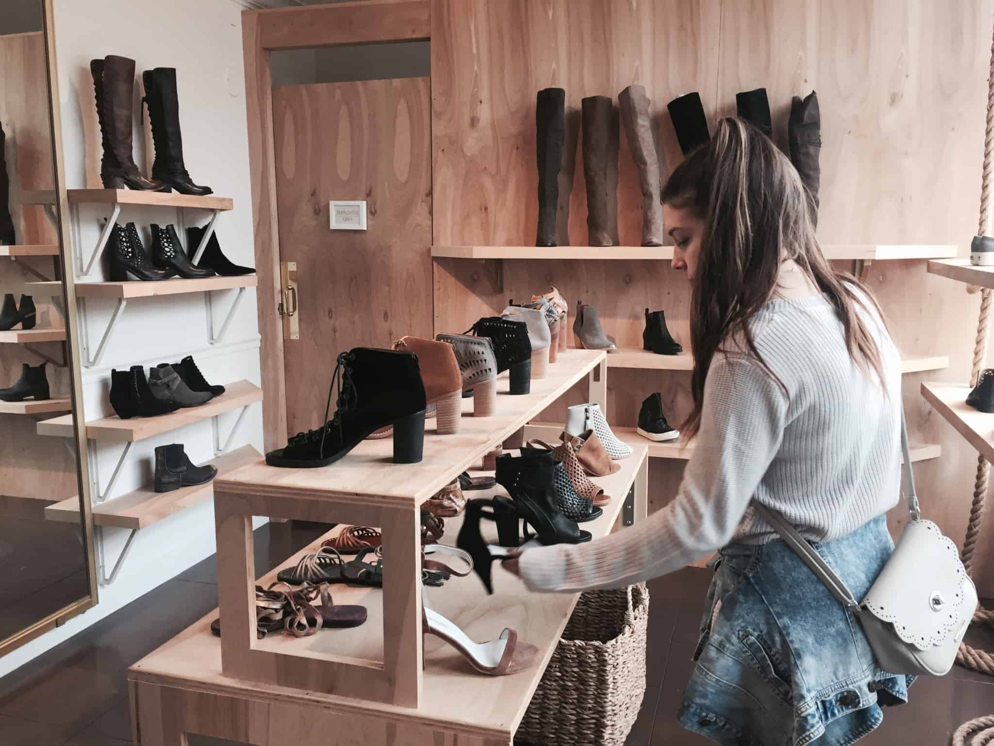 rapariga a ver uns sapatos pretos numa pequena loja