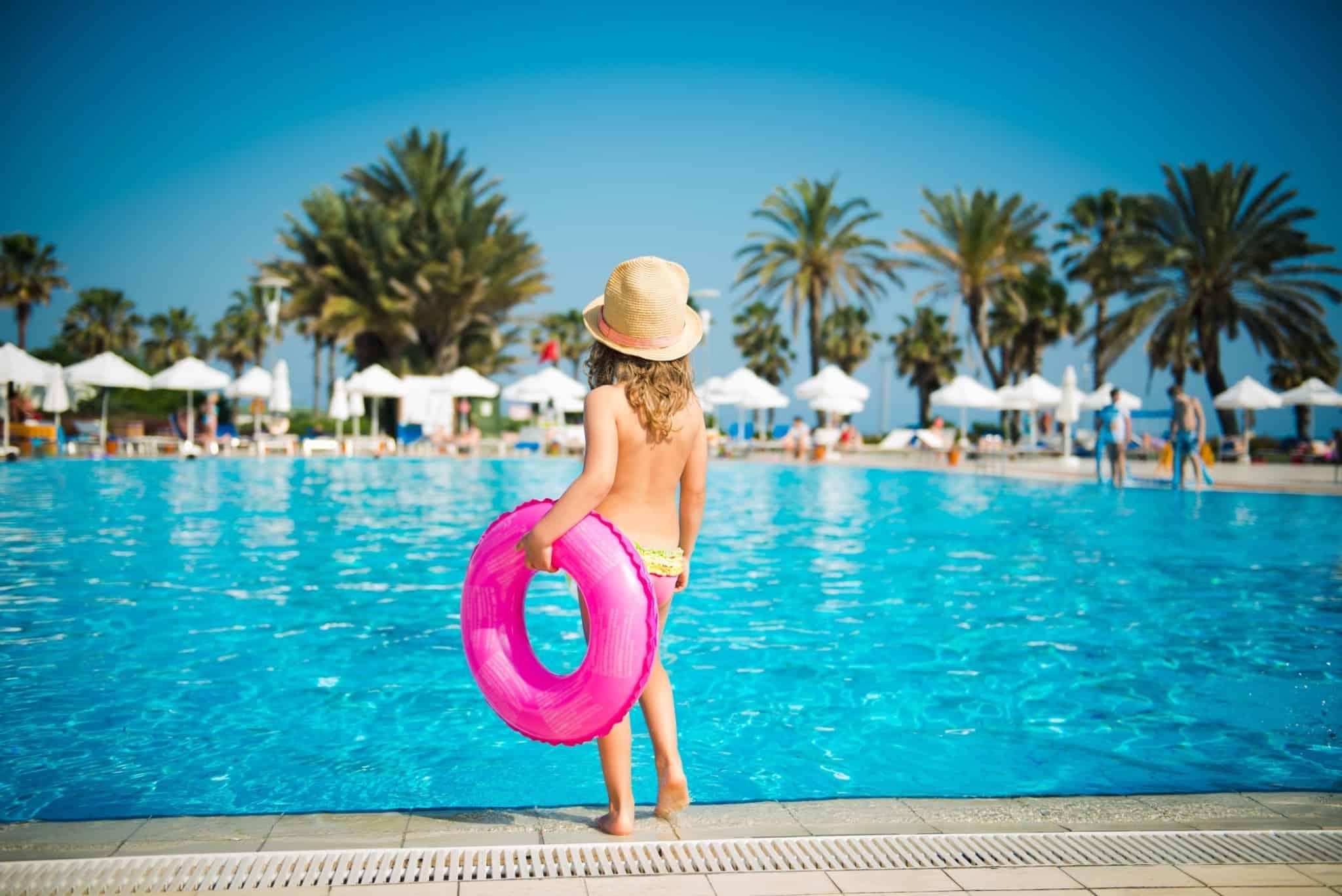 criança à beira da piscina com uma boia cor de rosa