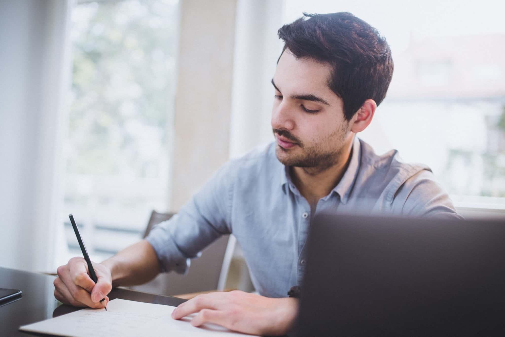 rapaz de camisa azul a escrever com uma caneta numa folha