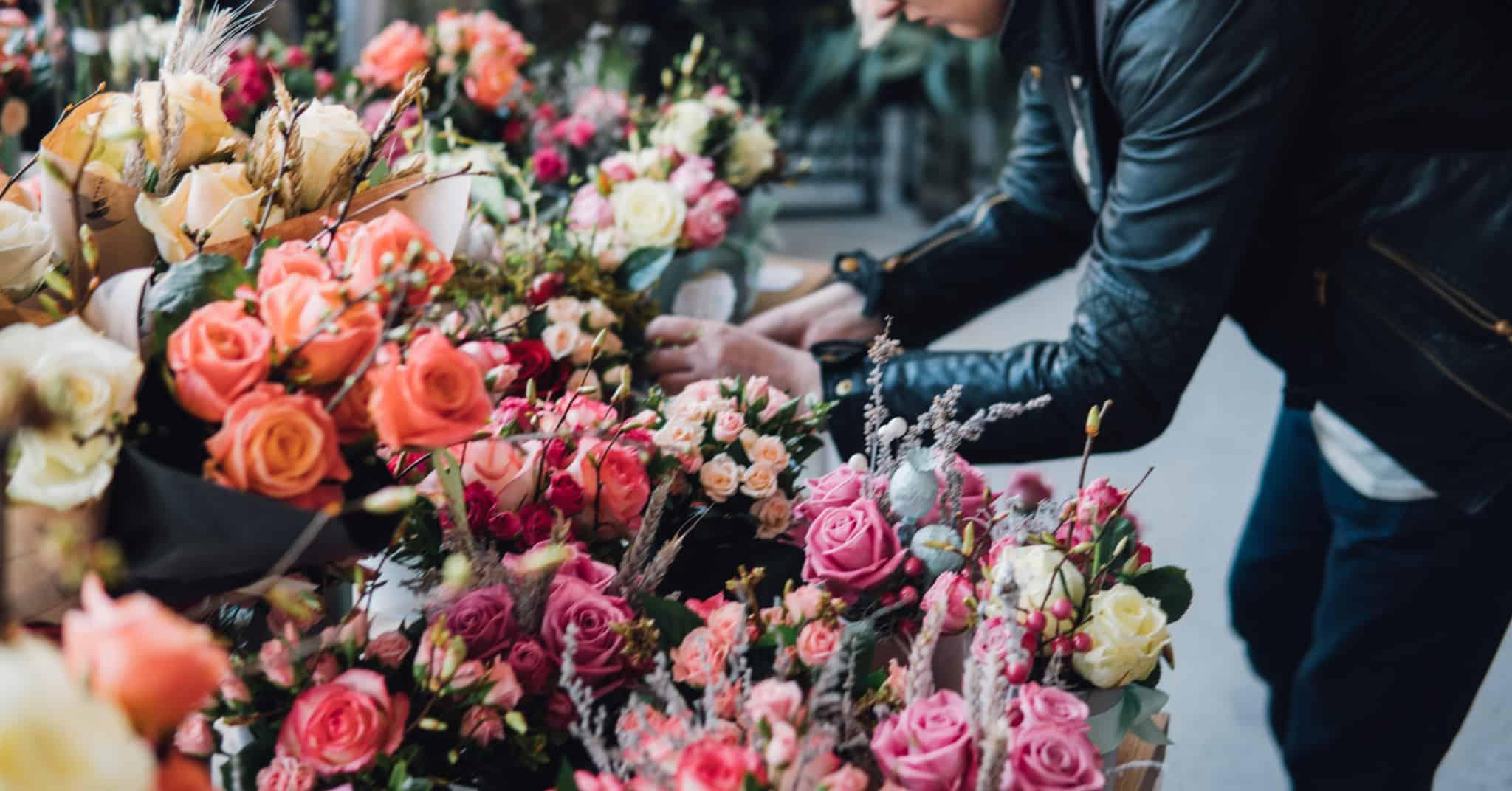 pessoa a arranjar flores num tributo