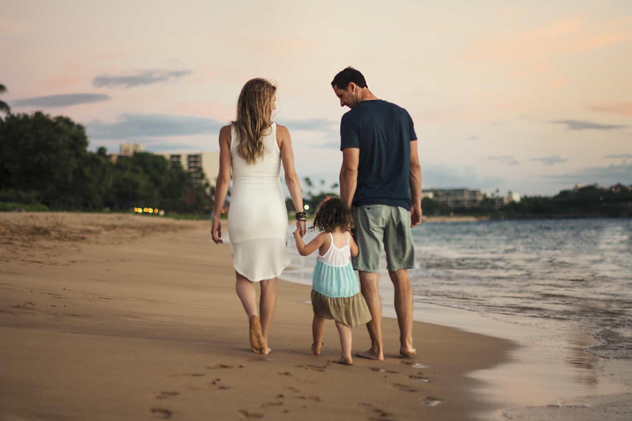 casal a passear na praia com a filha