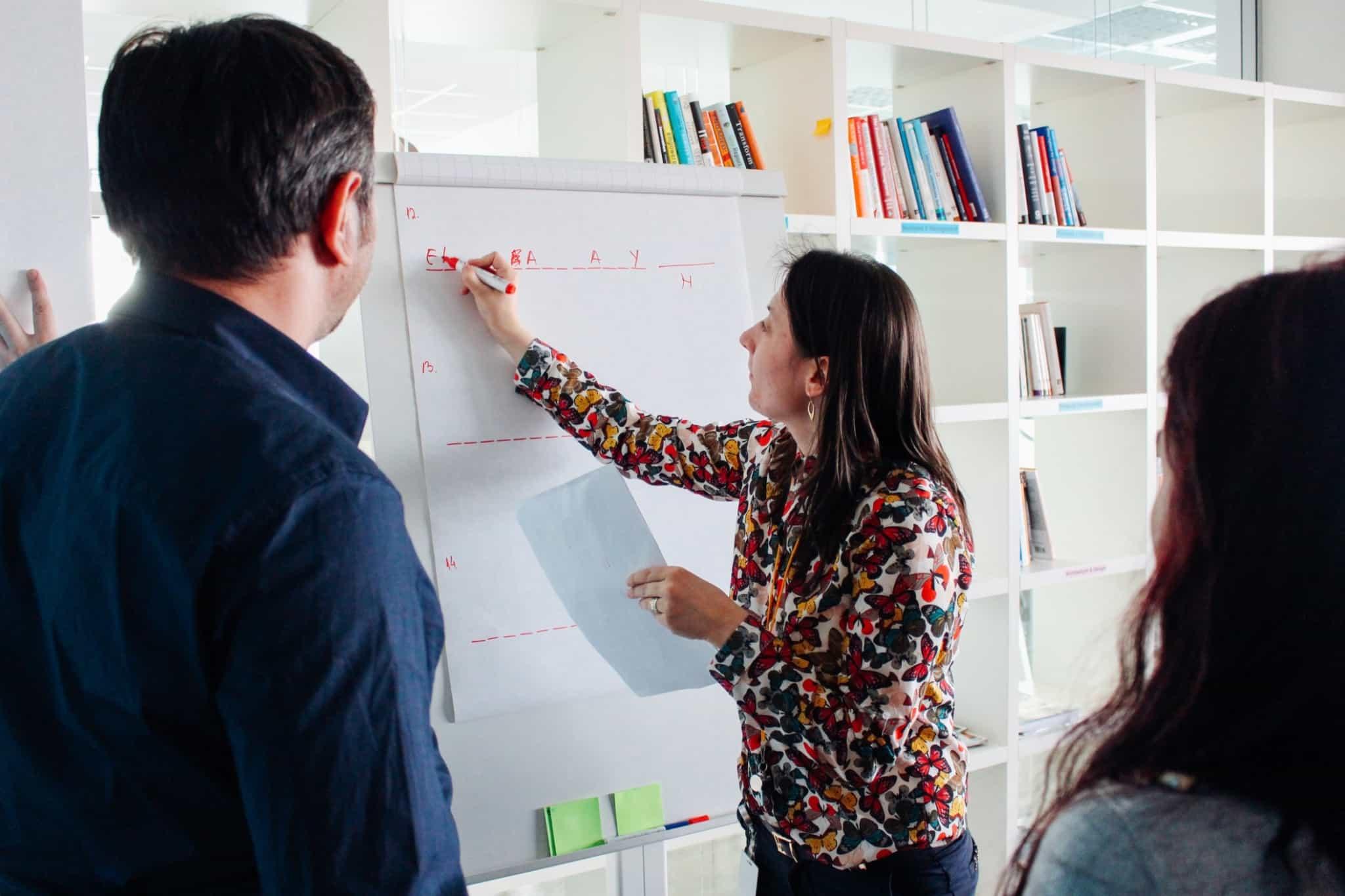 reunião de equipa em que uma mulher está a escrever num quadro branco