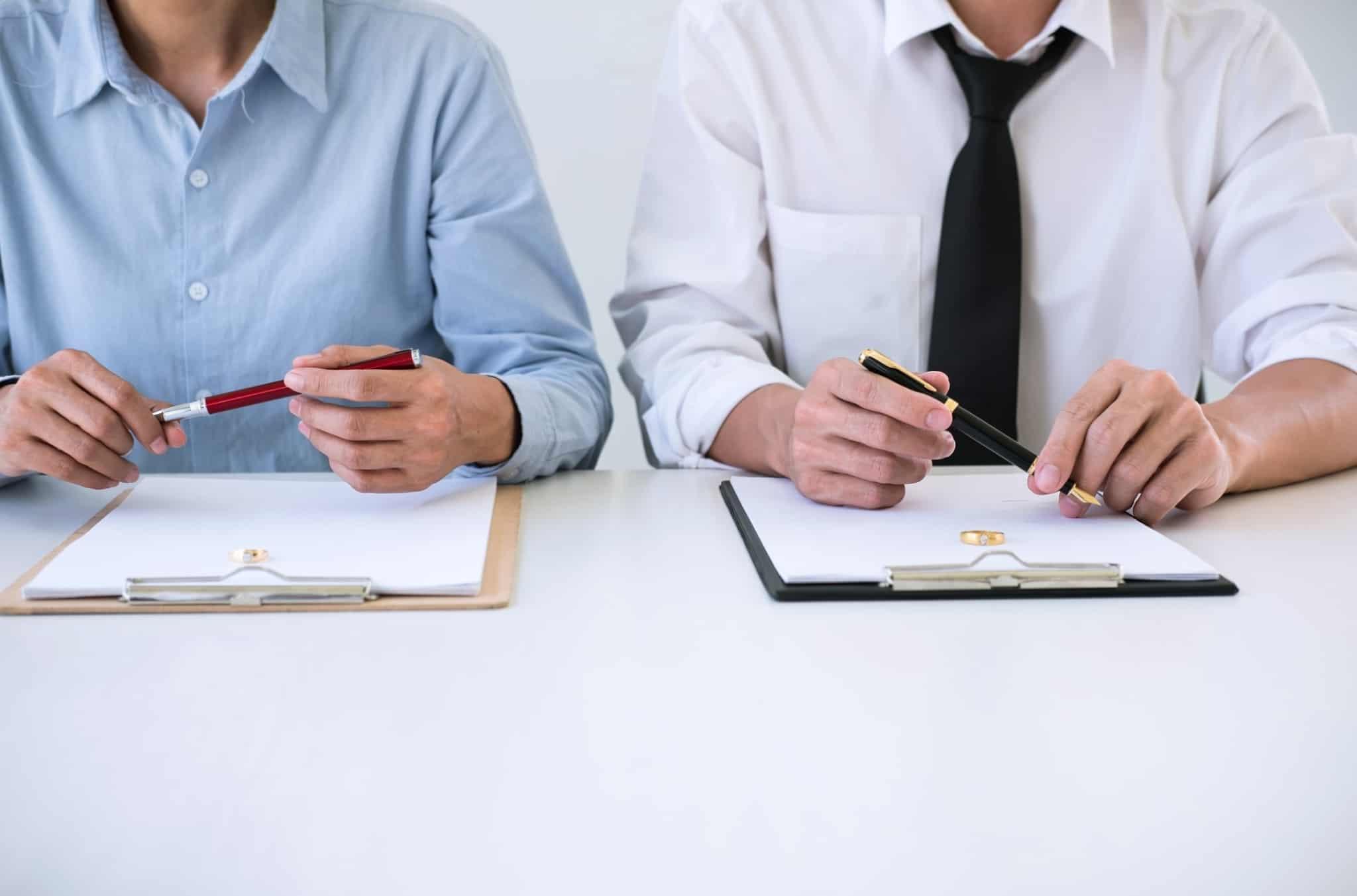 dois homens a segurar canetas para assinar contratos