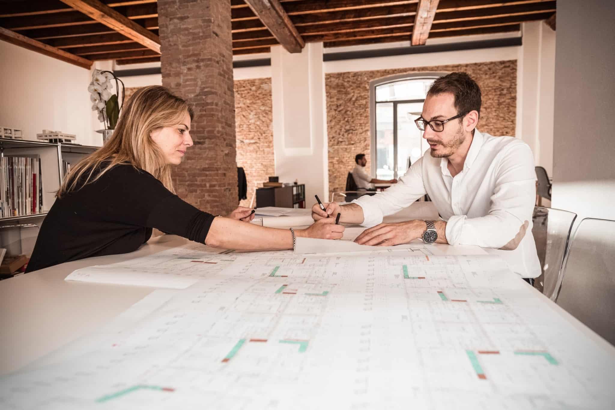 dois arquitectos a trabalhar num projecto em cima de uma mesa