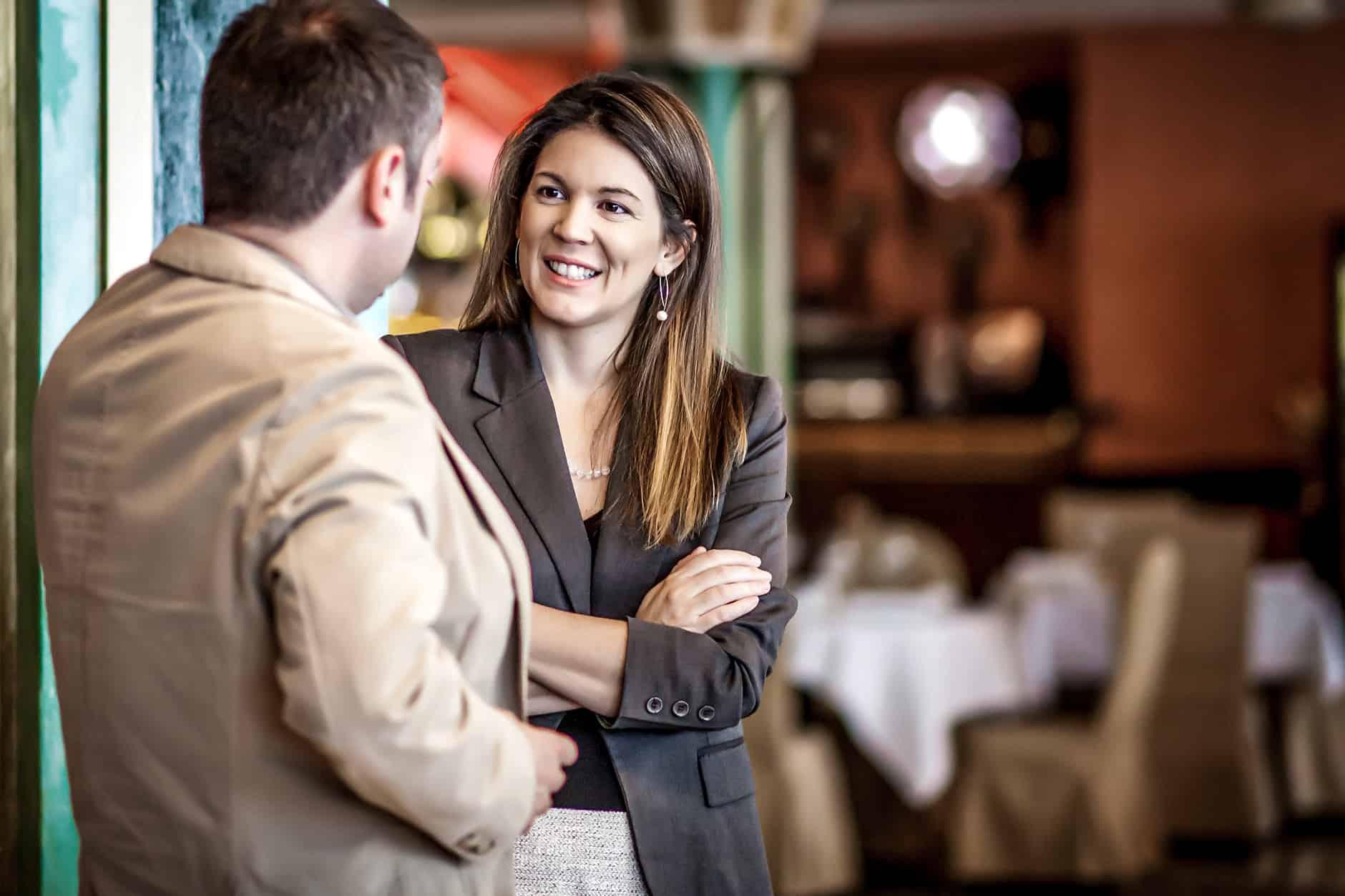 dois jovens, uma mulher e um homem, trocam conhecimentos em ambiente de networking profissional