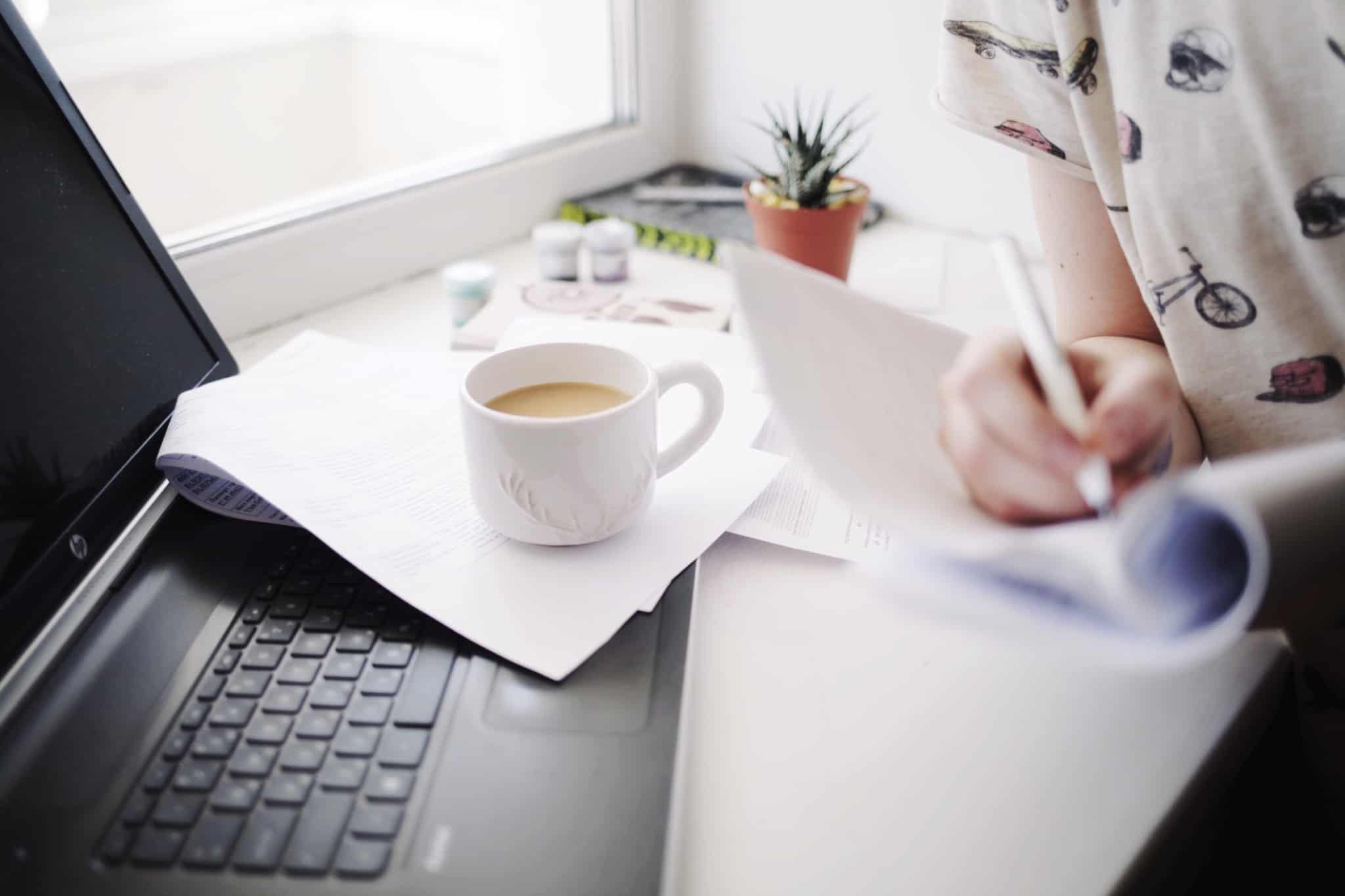 rapariga com uma chavena de cafe ao lado a escrever no bloco