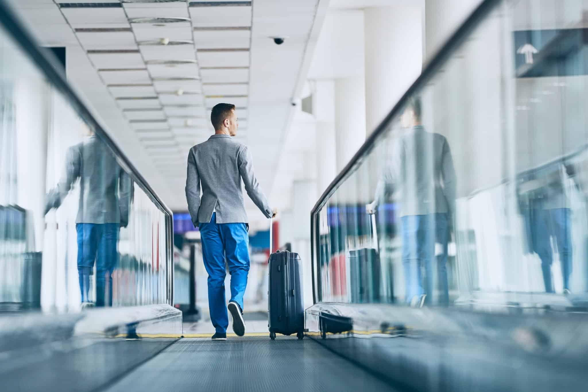 homem de blazer cinzento a andar nas escadas rolantes de um aeroporto
