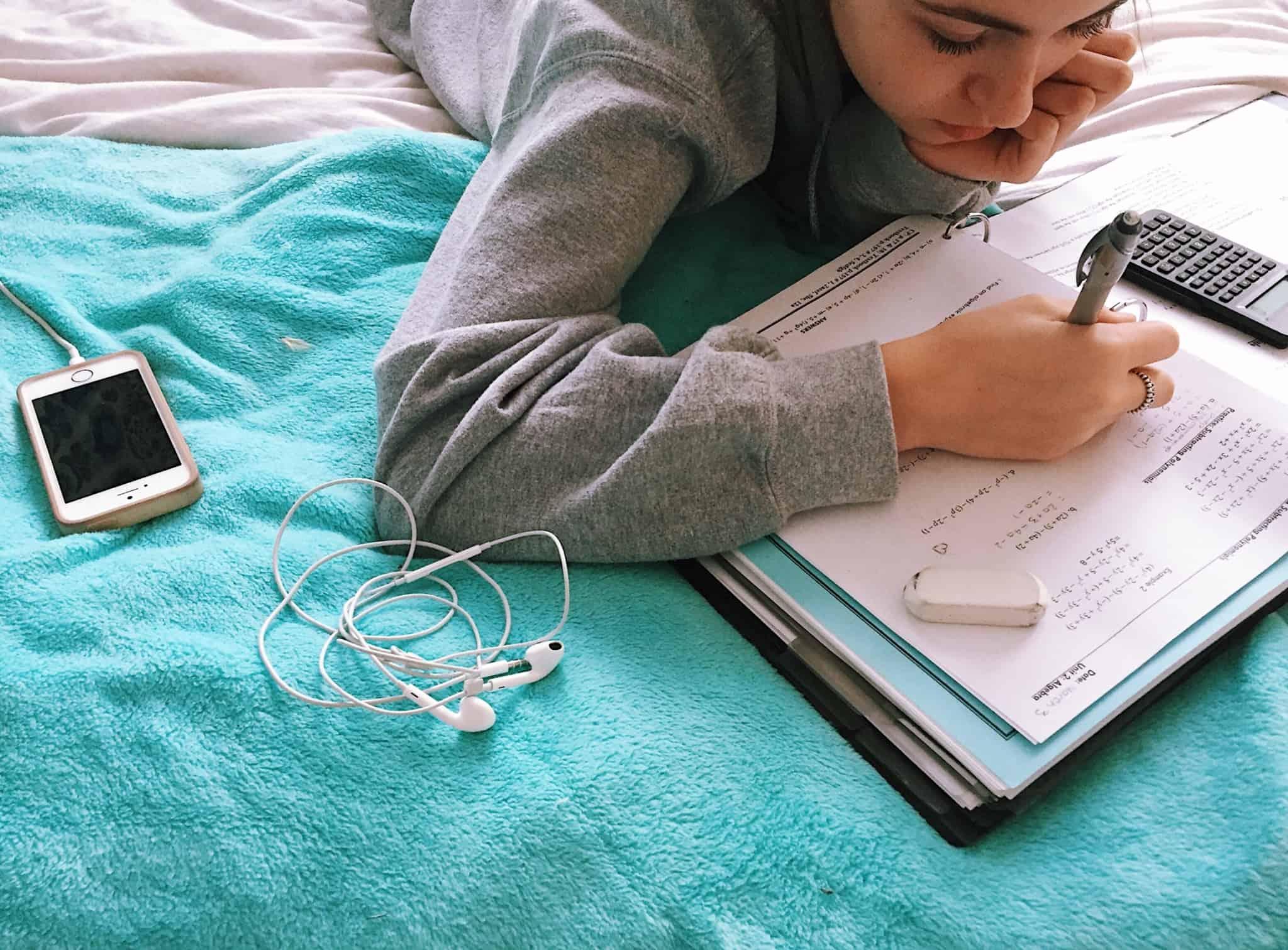 criança em cima da cama a fazer os trabalhos de casa de matemática