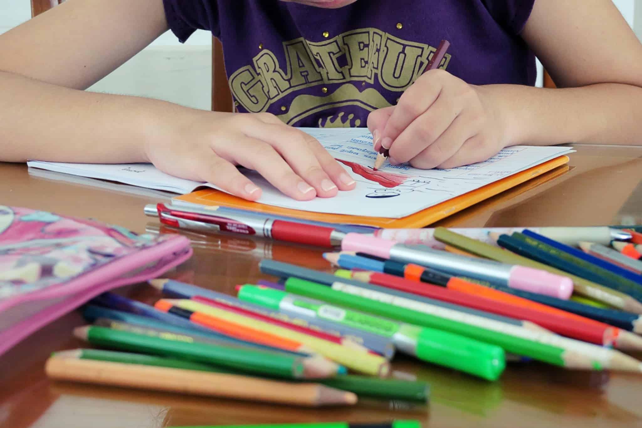 criança a pintar de vermelho num livro com vários lápis de cor em cima da mesa