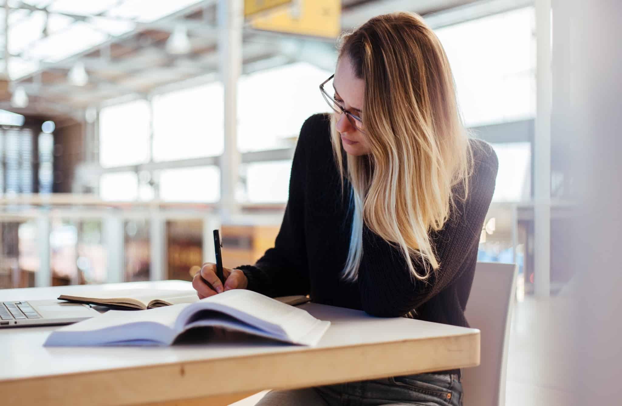 rapariga loira com camisola preta a escrever