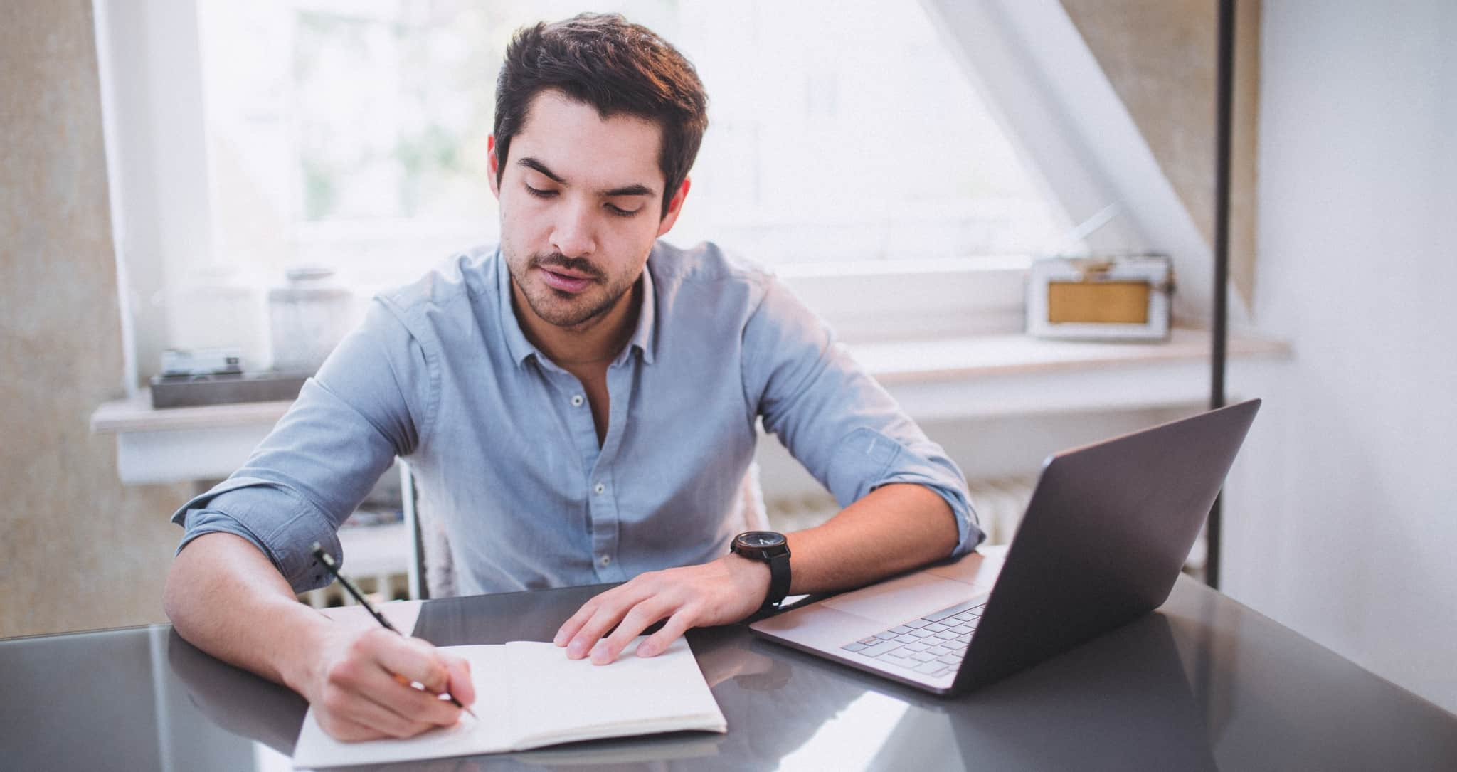 jovem a escrever com computador à frente