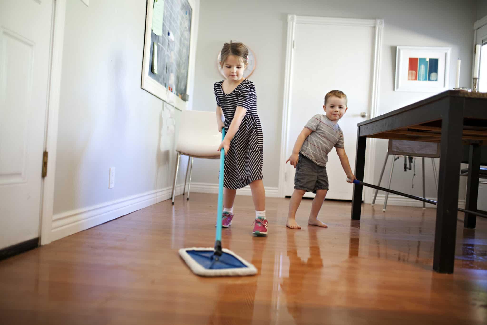 uma menina e um menino a lavar o chão