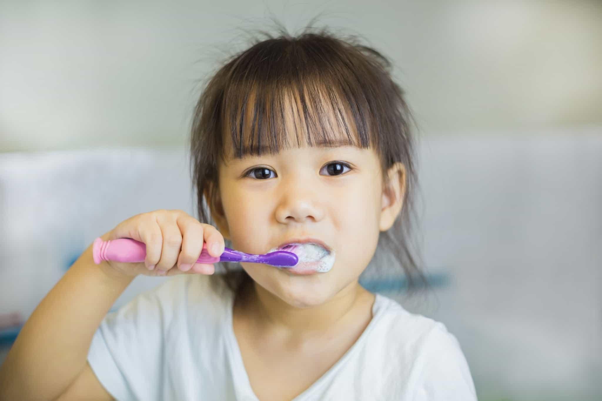 rapariga de franja a lavar os dentes