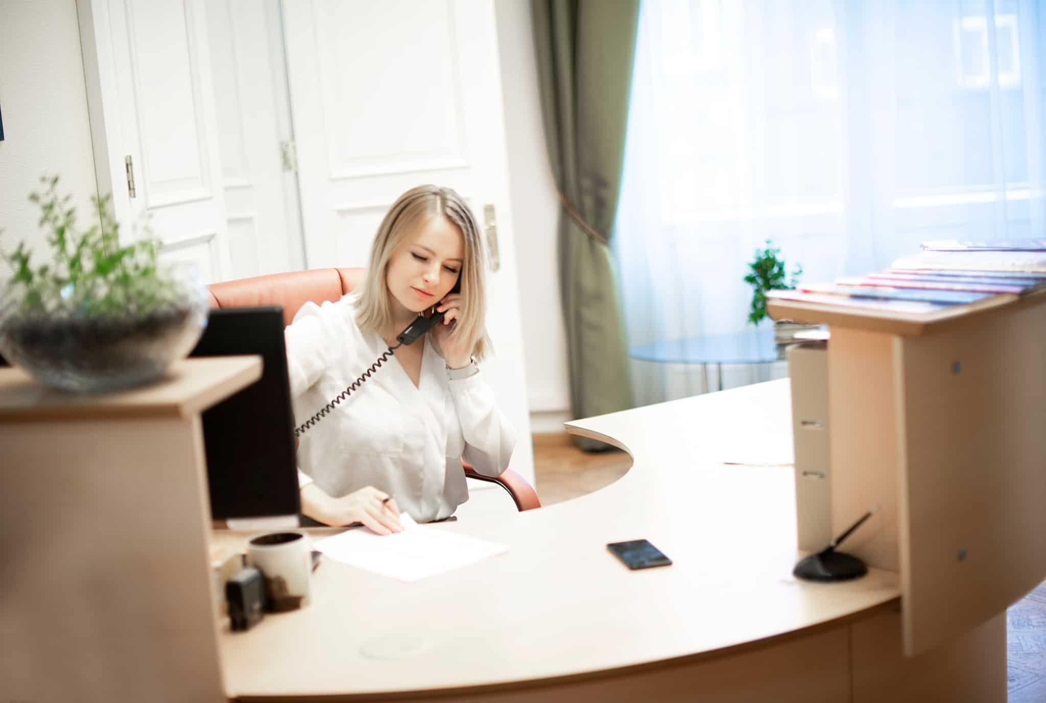 rapariga loira a atender o telefone no escritório
