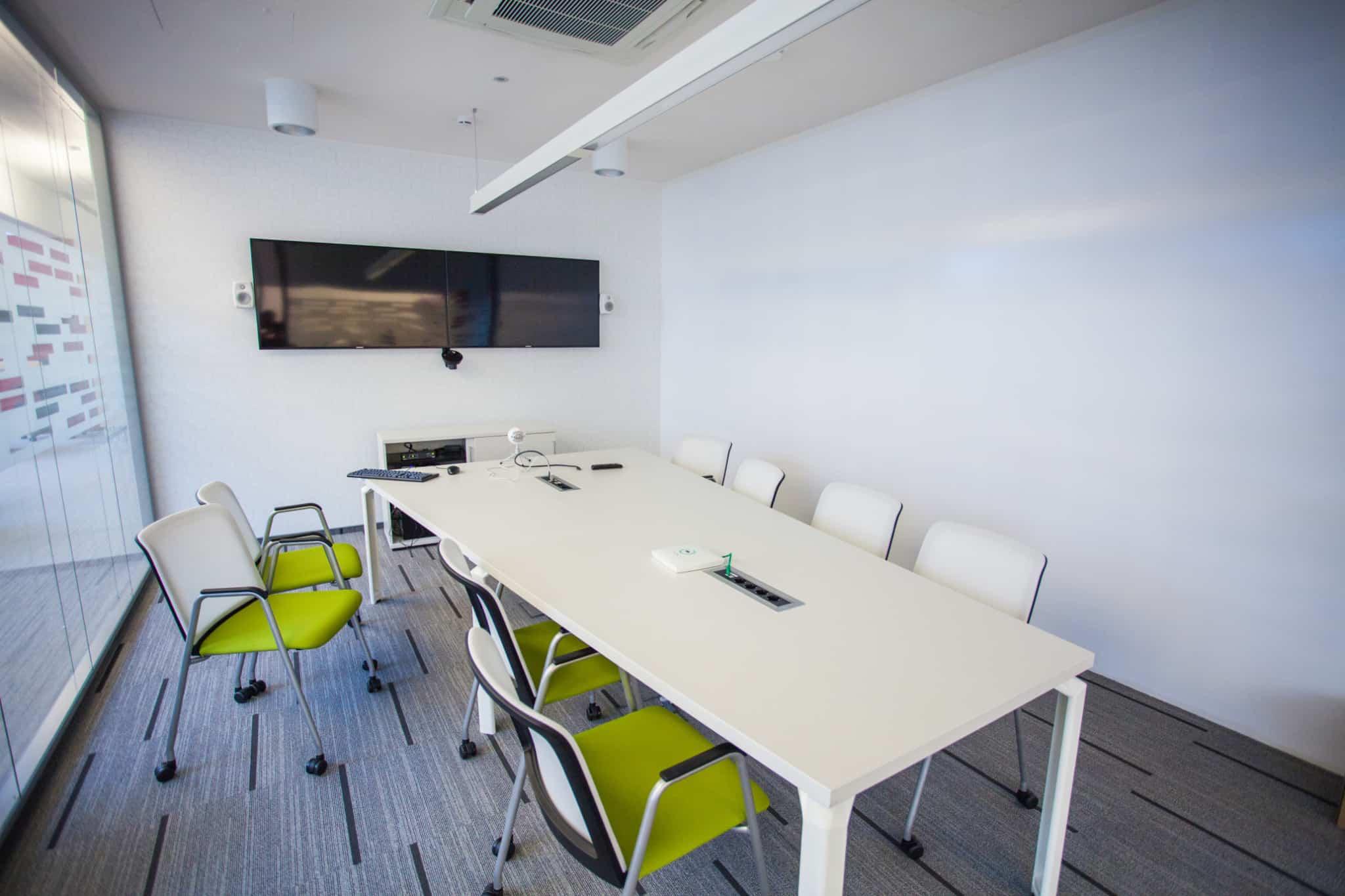 sala de reunioes vazia com mesa branca e várias cadeiras