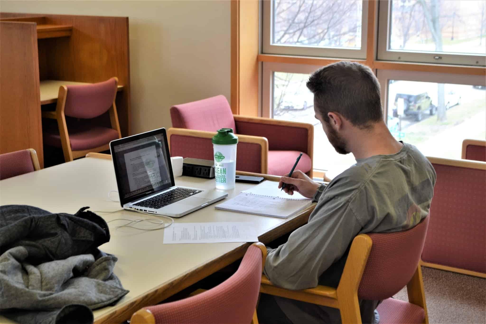rapaz estudante a trabalhar na biblioteca